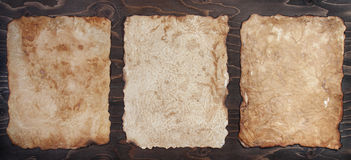 Three vintage papers on a wooden backround Stock Photos
