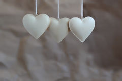 Three vintage shabby hearts on the background of old paper. Soft focus, background mode Royalty Free Stock Photography