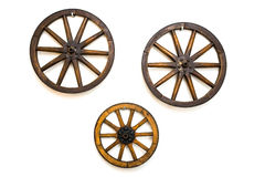 Three vintage wagon wheels on white wall Royalty Free Stock Photo
