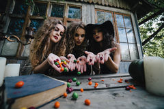Three vintage witches perform magic ritual. Throwing sweet at a table on the eve of Halloween Royalty Free Stock Photos