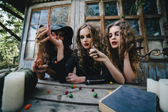 Three vintage witches perform magic ritual Royalty Free Stock Photography