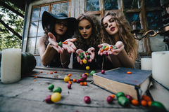 Three vintage witches perform magic ritual. Throwing sweet at a table on the eve of Halloween Royalty Free Stock Images