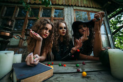 Three vintage witches perform magic ritual. Throwing sweet at a table on the eve of Halloween Stock Photos
