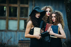 Three vintage women as witches. Pose in front of an abandoned building with books in hand on the eve of Halloween Royalty Free Stock Photos