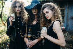 Three vintage women as witches. Pose in front of an abandoned building on the eve of Halloween Royalty Free Stock Photos