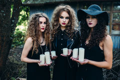 Three vintage women as witches. Poses and hold in their hands the candles on the eve of Halloween Stock Images
