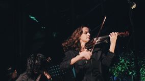 Three violinist fun and provocatively playing on stage. Excellent performance of the instrumental ensemble. Cool rock band. Beautiful violinist girls stock video footage