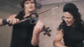 Three violinists with black clothes play in an unfinished room. Great musicians in the industrial landscape stock video footage