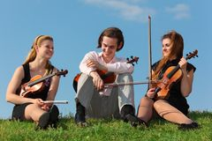 Three violinists sit on grass against sky. Three violinists sit on green grass against sky Stock Photos