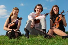 Three violinists sit on grass against sky. Three violinists sit on green grass against sky Royalty Free Stock Photo