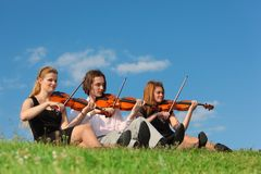 Three violinists sit and play on grass against sky. Three violinists sit and play on green grass against sky Stock Image