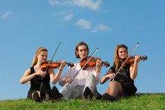 Three violinists sit and play on grass against sky. Three violinists sit and play on grass against blue sky Royalty Free Stock Image