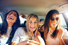 Three vivacious girlfriends on a road trip Stock Photos