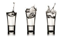 Three vodka glasses with splashes. Clipping path is included Stock Photography