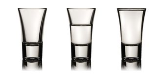 Three vodka glasses. With various level of liquid - empty, half and full, clipping path is included Stock Images