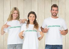 Three volunteer pointing at message printed on their tshirt Royalty Free Stock Photo