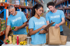 Three volunteers packing eatables in cardboard box in a warehouse Stock Images