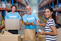 Three volunteers packing eatables in cardboard box. In a warehouse stock images