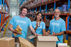 Three volunteers packing eatables in cardboard box. In a warehouse royalty free stock photo