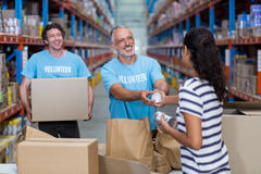 Three volunteers packing eatables in cardboard box. In a warehouse royalty free stock photography