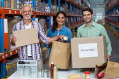 Three volunteers packing eatables in cardboard box. In a warehouse stock photos