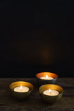 Three votive candles. In copper or golden votive candle holders Stock Image