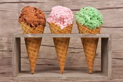 Three waffle cones of ice cream in rustic holder over wood. Chocolate, cherry and pistachio ice cream in waffle cones in rustic holder over a wood background Royalty Free Stock Photography