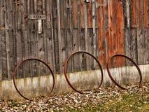 Three wagon wheel rims. Rusting cast iron wagon wheels leaning against barn wall stock photos