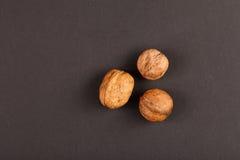 Three walnuts on black paper Royalty Free Stock Photo
