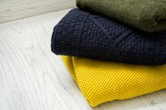 Three warm colour sweaters on a wooden background. Fashionable c Stock Photography