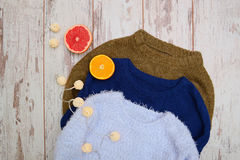 Three warm sweater on a wooden background. Garland, orange and grapefruit. Fashionable concept Royalty Free Stock Photography