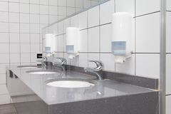 Three washbasins in the washroom, with white tiled walls stock image