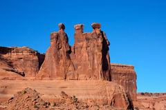 Three Watchers. Taken at Arches National Park, this natural rock formation appears to be three figures peering off into the horizon royalty free stock images