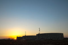 Agricultural Water Tanks at Sunset. Three water reservoir storage tanks in the middle of a cropped field at sunset Royalty Free Stock Photography