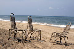 Three wattled chairs stand on a beach, wait for people against the sea. GOA India beach Stock Photos