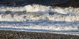 Three waves coming ashore on beach at Fleetwood. Three waves coming ashore on the beach at Fleetwood on the edge of Morecambe Bay, Lancashire, England on a windy stock photos