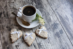 Three wedding cookies decorated white sesame with a cup of coffee. Retro style. Royalty Free Stock Photography