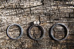 Three wedding rings on a wooden background.  Royalty Free Stock Photos