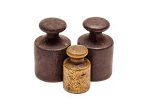 Three weights, one bronze. Set of three antique calibration weights, isolated on white background Stock Photos