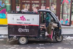 Three-wheel motor scooter with a cab on the streets of Hunchun in China royalty free stock photo
