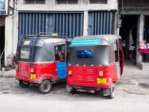 Three-wheel taxis parking at the roadside in Colombo, Sri Lanka. Colombo, Sri Lanka - November 11, 2017: Two red three-wheeled taxi parking at the roadside in royalty free stock photos