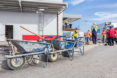 Three wheelbarrows with tools for cleaning are lined up Stock Images