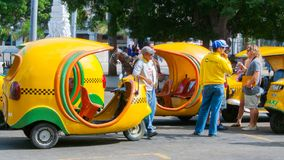Three wheeled taxi called coco taxi havana near by street dragon royalty free stock photos