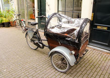 Three wheels bicycle with casing cover. Three wheels black retro bicycle with wooden casing cover on a street of Amsterdam Stock Photography