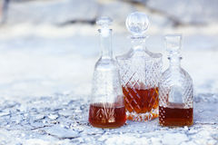 Three whiskey decanters against a light gray background Royalty Free Stock Photo