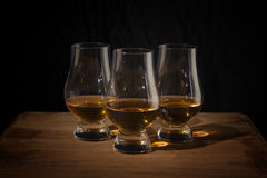 Three whisky glasses on a wooden table Royalty Free Stock Photo