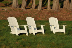 Three white adirondack chairs in a field Stock Images