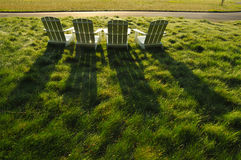 Three white adirondack chairs in a field Royalty Free Stock Images