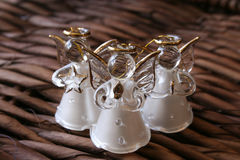 Three White Angels. Three white glass angels on a rustic background Royalty Free Stock Image