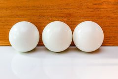Three white balls of billiard over wooden board Royalty Free Stock Image